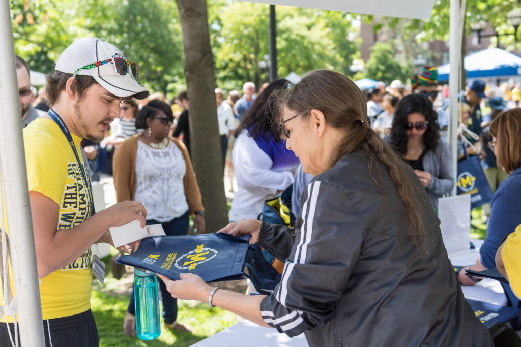 A staff member receives a free gift at MSTAFF200